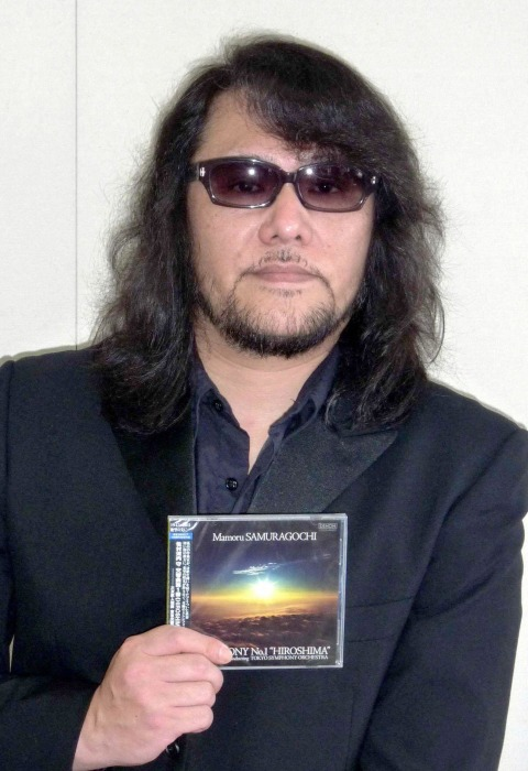 "Image: File photo of Mamoru Samuragochi, a famous Japanese classical composer who has been called ""Japan's Beethoven"", posing with a CD of Symphony No. 1 ""Hiroshima"""