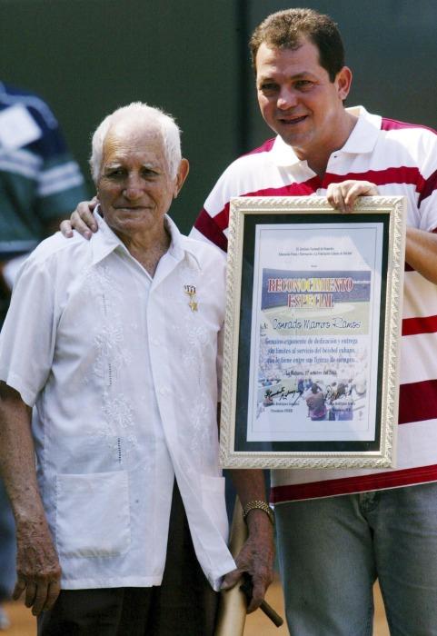 Image: File photo of veteran baseball player Conrado Marrero standing next to Humberto Rodriguez, president of the Cuban Sports Federation in Havana