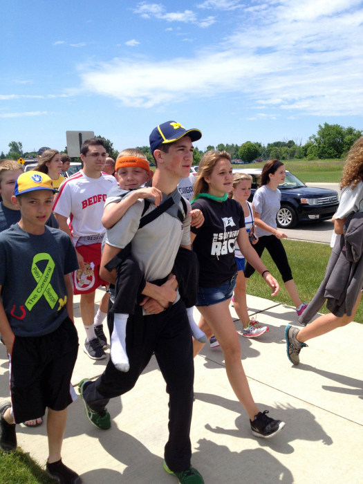 """Image: Hunter Gandee, 14, walks in Saline, Mich., on Sunday, June 8, 2014, during the second day of his two-day, 40-mile """"Cerebral Palsy Swagger"""" walk"""