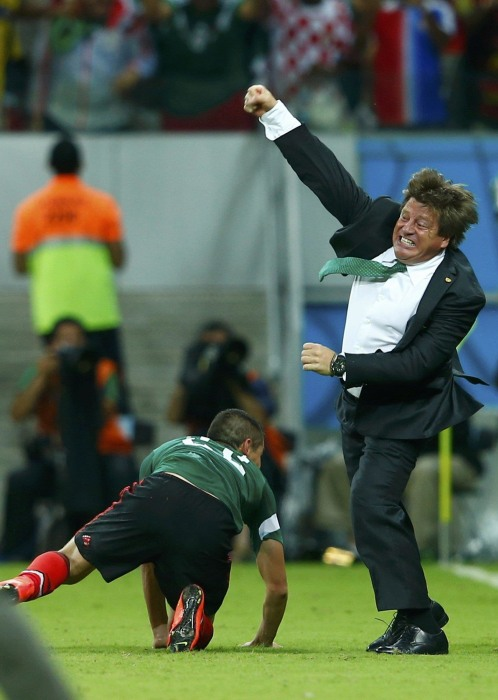 Image: Mexico's coach Miguel Herrera (R) celebrates the goal of Andres Guardado (not pictured) during their 2014 World Cup Group A soccer match against Croatia at the Pernambuco arena in Recife