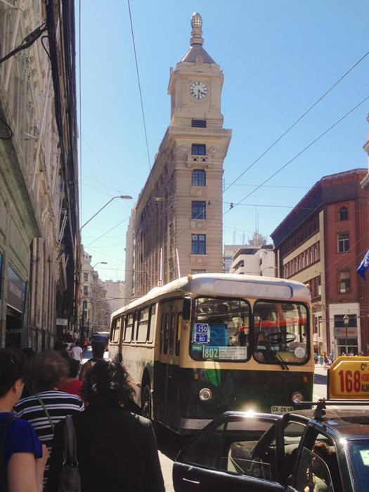 Image: A trolleybus and the Turri Clock Tower behind it in the Financial District of Valparaiso, Chile.