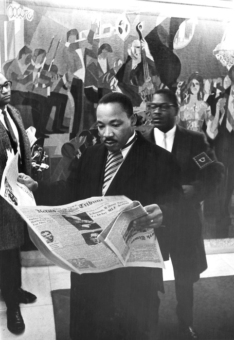 Image: Martin Luther King Jr. Reads the newspaper as he prepares to  accept his Nobel Prize Award in 1964 in this handout image