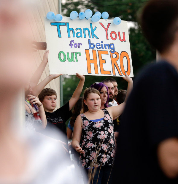 Image: Mourners hold a sign during a vigil at Lakefront Park