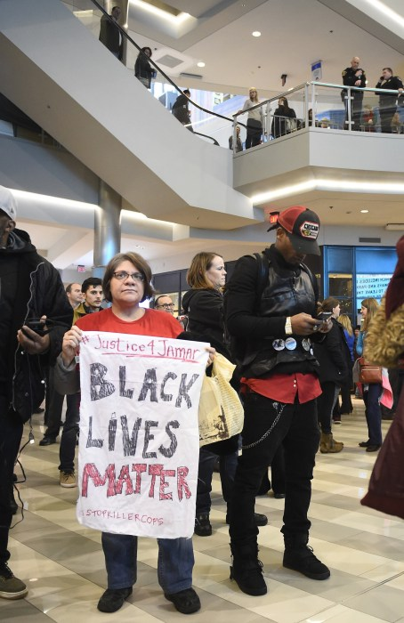 Image: Jess Sedin of Minneapolis held a sign during a Black Lives Matter protest at the Mall of America in Bloomington