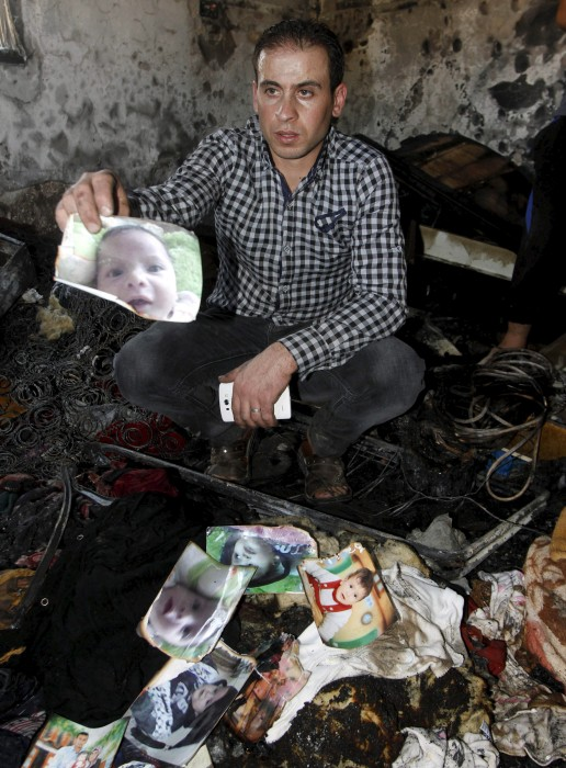 Image: Relative of 18-month-old Palestinian baby Ali Dawabsheh, who was killed after his family's house was set to fire in a suspected attack by Jewish extremists, shows his picture at the burnt house in Duma village near the West Bank city of Nablus