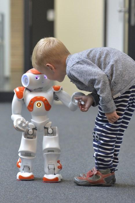 Image: A child with language robot Nao