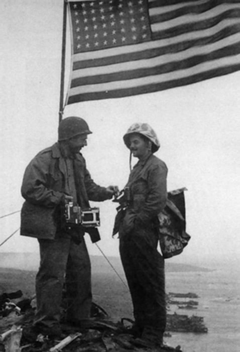 AP photographer Joe Rosenthal, left, and Army Pfc. George Burns pose under the second flag raised on Iwo Jima's Mount Suribachi.