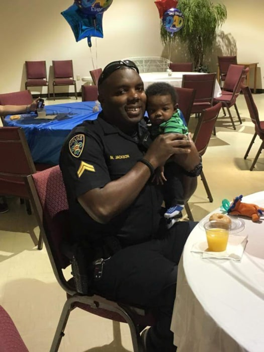 Image: Baton Rouge Police Officer Montrell Jackson, holds his son Mason at a Father's Day event for police officers in Baton Rouge