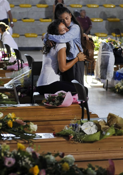 Image: Two girls embrace in Ascoli Piceno, central Italy, Saturday, as they wait  for the start of a mass funeral for some earthquake victims.