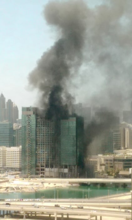 Image: Smoke rises from a blaze in a high-rise building under construction in Abu Dhabi, United Arab Emirates.