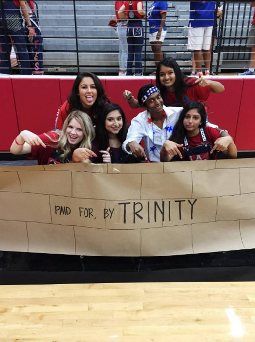 """Image: Students with a pep rally sign that depicts the """"wall"""" Donald Trump wants to build along the Mexican border"""