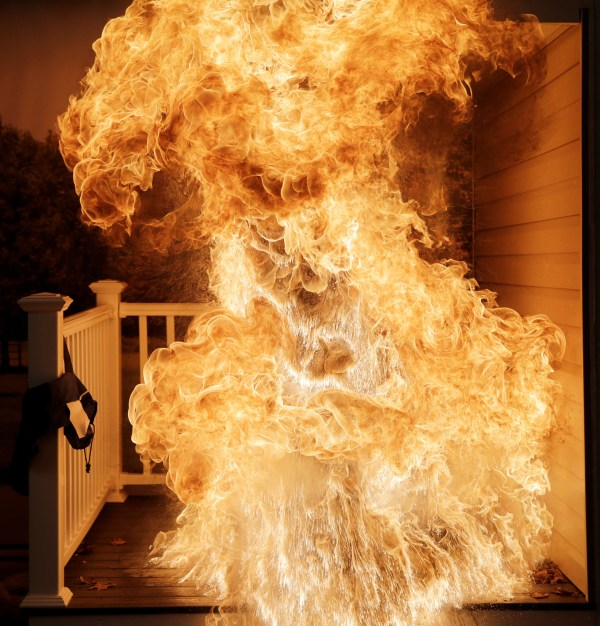 Image: Frozen turkey is dropped into a deep fryer, creating a large fireball, at a food safety demonstration in Rockville