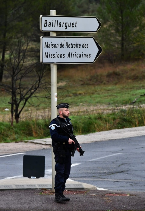 Image: A police officer stands guard on a road in Montferrier-sur-Lez, France