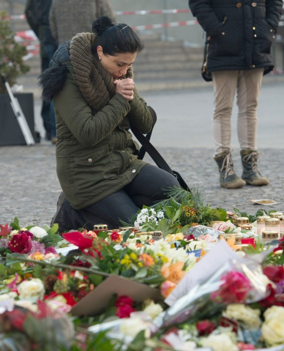 Image: A woman kneels near the site of the attack at the Christmas market