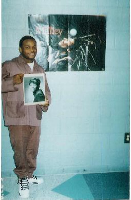 Image: Jimmy Dennis poses while holding a photograph of his mother.