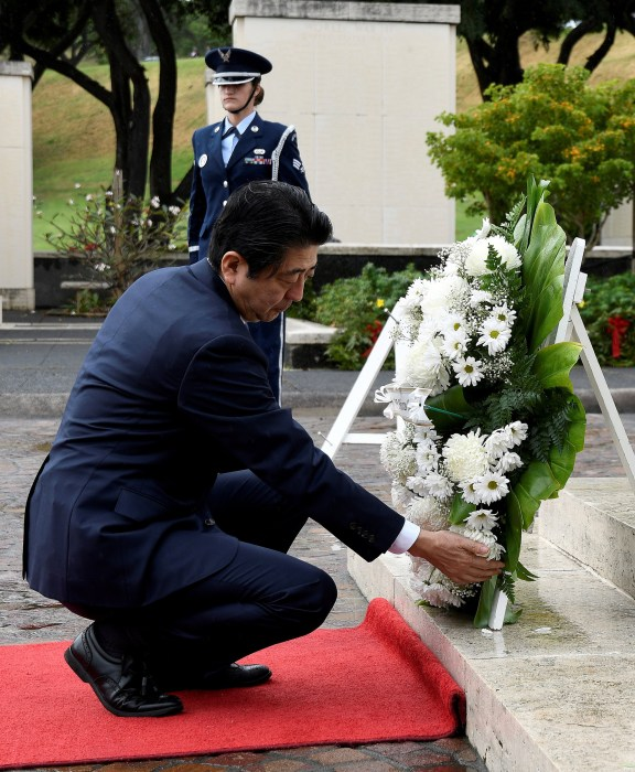 Image: Japanese Prime Minister Shinzo Abe presents a wreath at the National Memorial Cemetery of the Pacific at Punchbowl in Honolulu