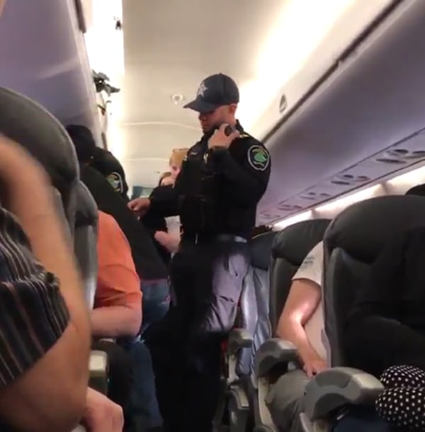 Image: Security stand in the aisle before forcibly removing a United Airlines passenger from a plane