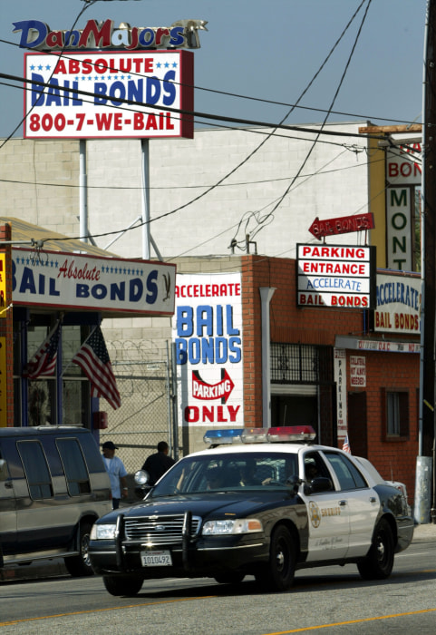 Image: A Los Angeles County Sheriff's car drives past bail bonds businesses