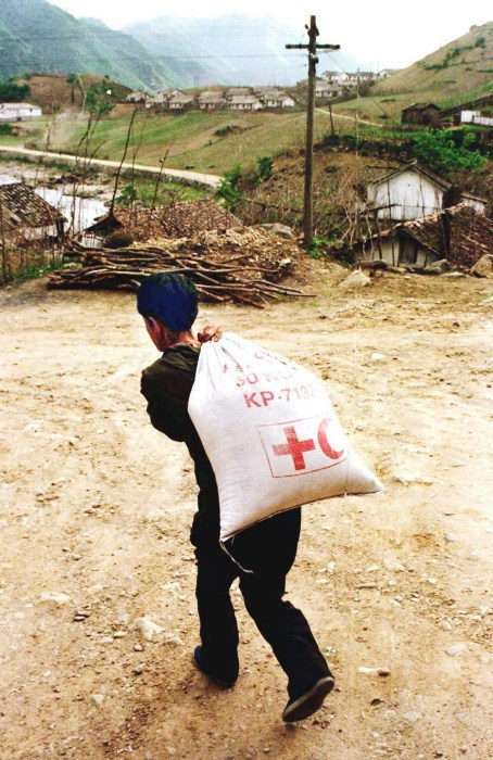 Image: A North Korean carries a sack containing Red Cross rations in 1997