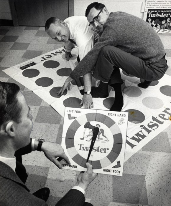 "In a Dec. 16,1966 photo, co-inventors of the game ""Twister"" Charles Foley, left, and Neil Rabens demonstrate the game for Charles McCarty, foreground, president of Research and Development, Inc., in Minnesota."