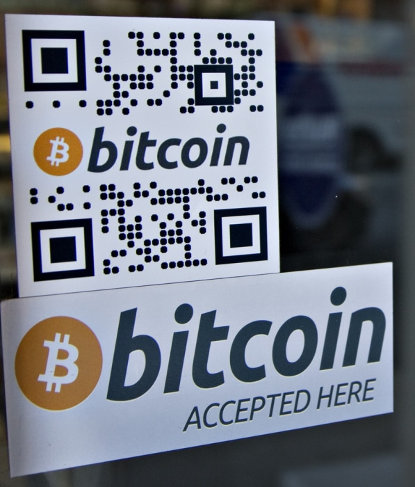 Signs on window advertise a bitcoin ATM machine that has been installed in a Waves Coffee House in Vancouver, British Columbia October 28, 2013. The n...