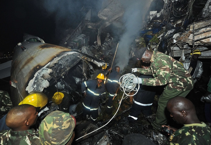 Image: Policemen and firefighters search in the wreckage of a cargo plane