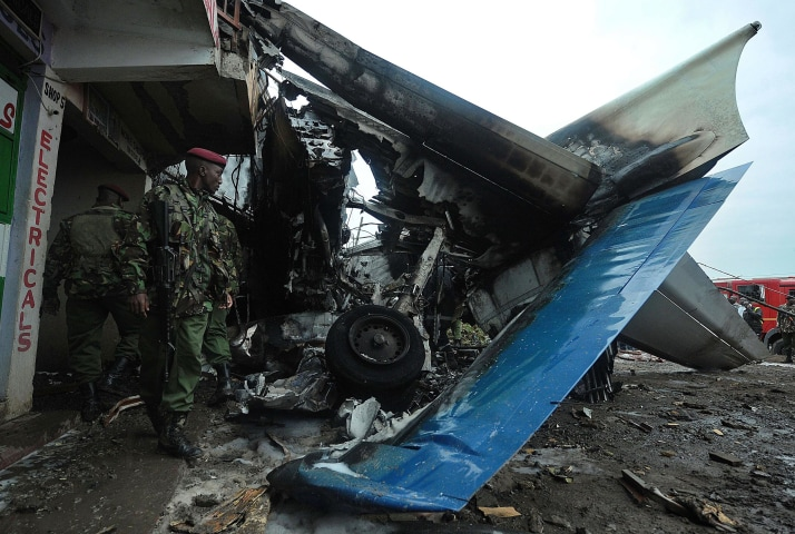 Image: Kenyan army men stand near the wreckage of a cargo plane