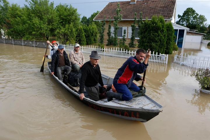 Image: Bosnian people are rescued from their flooded houses by boat