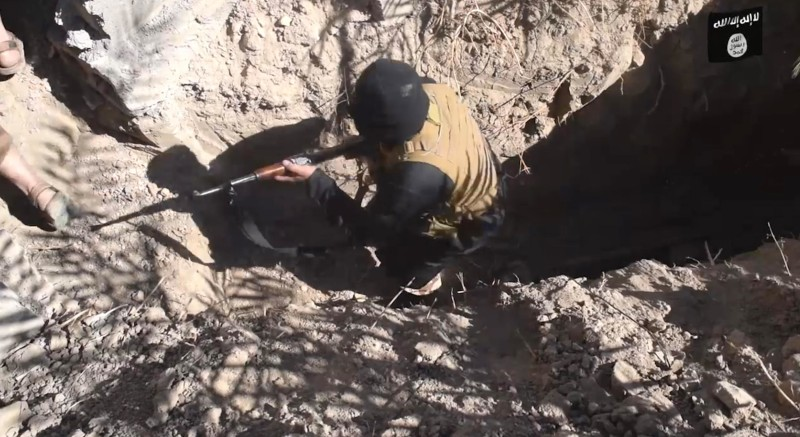 Image: ISIS fighters sit in a cave.