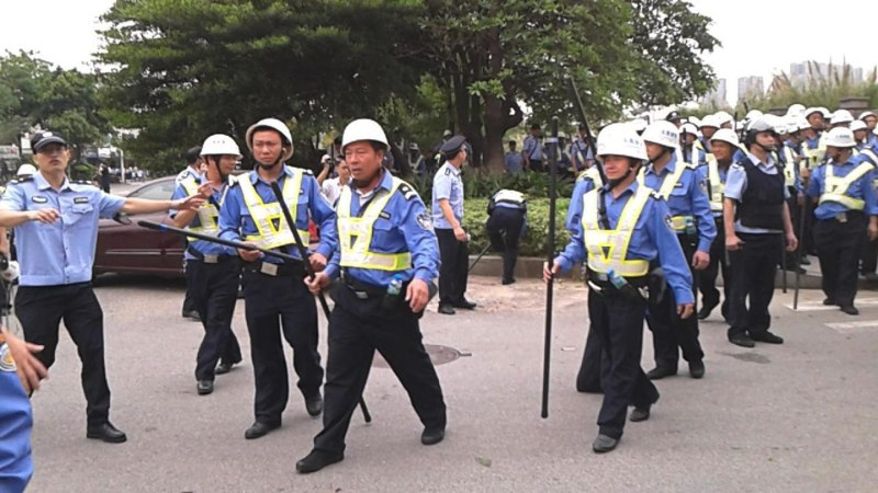 Police patrol as workers go on strike outside the Yue Yuen Industrial factory in Dongguan, China, on April 15.