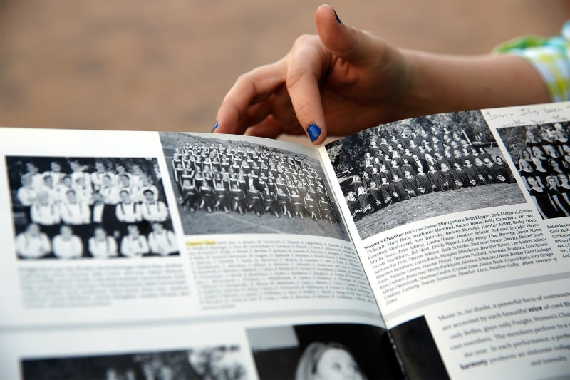 Image: Former Columbine High School students Jennifer Hammer points out their choir group picture in her yearbook to Heather Egeland at the Columbine Memorial