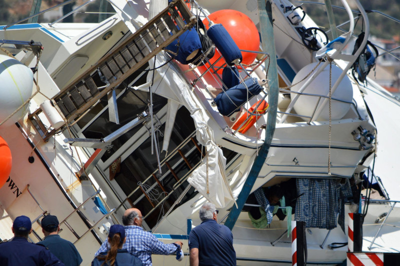 Image: A crane lifts a yacht after it capsized off the Greek island of Samos on Monday