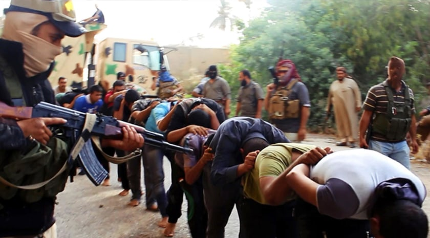 Image: Militants from ISIL lead away captured Iraqi soldiers in plain clothes after taking over a base in Tikrit