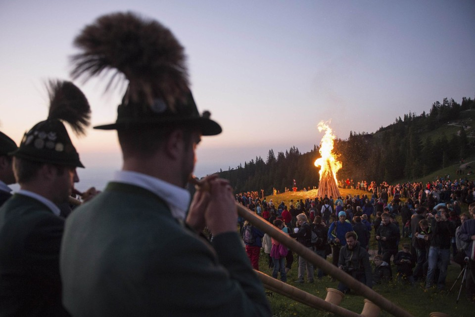 Image: Alphorn blowers perform in front of a bonfire during the Sonnwendfeuer Festival at Mt. Kampenwand