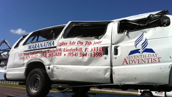 A damaged church van is towed away Saturday after it rolled over in Lee County, Fla