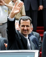 Syrian President Bashar al-Assad waves at a crowd at the parliament after delivering a speech in Damascus