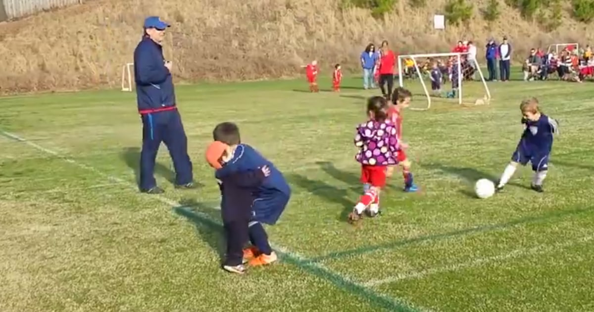 Little boy stops playing soccer to give brother an