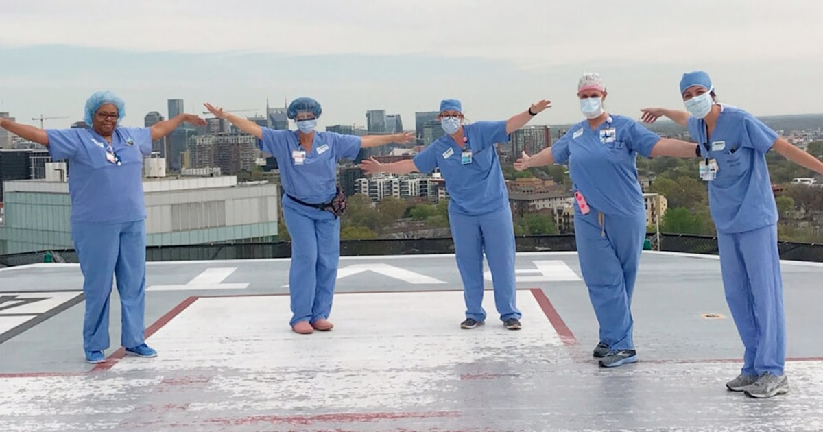 Nurses in scrubs and face masks with arms outstretched on top of helipad