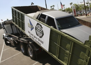 "Image: A truck removes a clunker vehicle in a dumpster from the parking lot of Courtesy Chevrolet during the last day of the ""Cash For Clunkers"" auto rebate program in Phoenix"