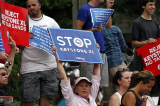 Protesters rally about the Keystone XL oil pipeline along U.S. President Barack Obama's motorcade as he arrives at the Jefferson Hotel in Washington