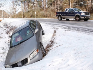 Image: Driver uses a mobile phone in a car after running off the roadway due to a snow storm in Atlanta