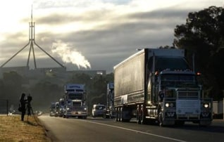 Convoy of trucks protesting against the Australian government's proposed carbon tax drive past Parliament House in Canberra