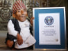 Image: Chandra Bahadur Dangi, 72, poses for a picture with his certificate after being announced as the world's shortest man living, as well as shortest person ever measured by the Guinness World Records, in Kathmandu