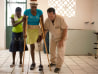 Image: Image: Chistela Eliance, 20, walks with her prosthetic leg for the first time with Jay Tew of Hanger Orthopedics, on right, in Cange, Haiti.