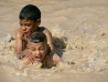 Boys play in a pool of water leaking from a broken pipe in Baghdad