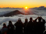 Image: Visitors watch the sun rise at 10,000 feet in Haleakala National Park in Maui, Hawaii.