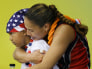 Ah Mow-Santos of the U.S. embraces her son Jordan after the women's preliminary pool A volleyball match against China at the Beijing 2008 Olympic Games