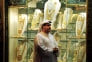 A man walks past a shop displaying gold wedding jewelry for Arabs at the Dubai Gold Souk.