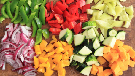 Colored peppers and onions diced on a chopping board;