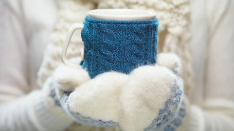 Mittens holding knitted cup